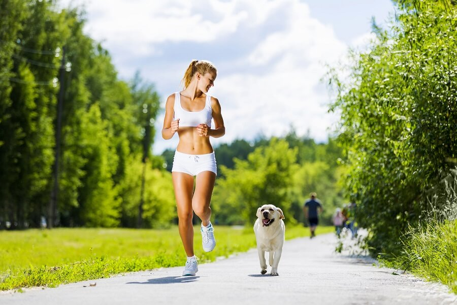 girl running in the park with her dog