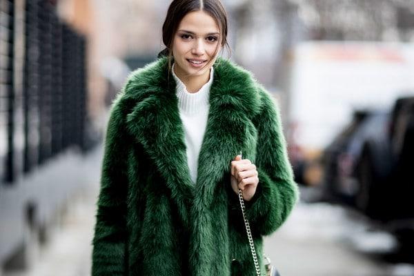 A brunette woman wearing a green fur coat